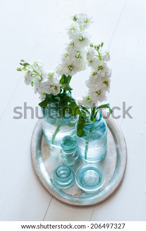White matthiola flowers in vintage glass bottles vases in an antique silver tray on wooden floor, home decoration, interior details - stock photo