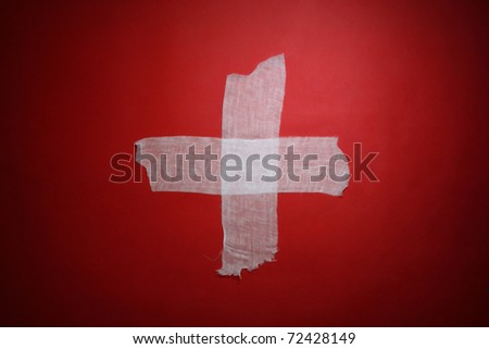 White medical cross from bandage on a red background - stock photo