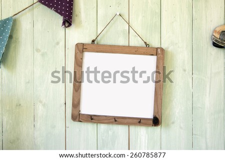 White message board hanging on retro green wooden wall background - stock photo