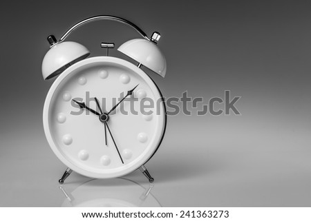 White metal alarm clock with two bells on grey gradient background, with copy space - stock photo
