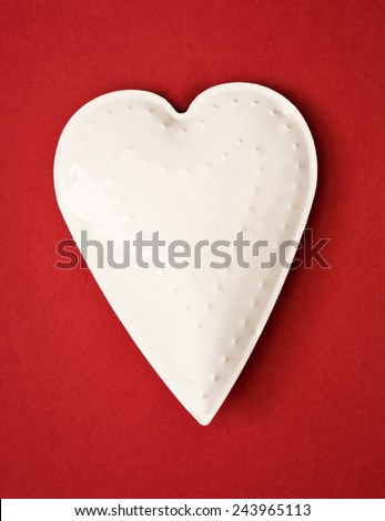 White metal heart on the red background. Valentine's Day. - stock photo
