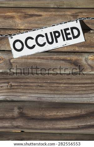 white metal sign with the word occupied hanging at a chain  in front of a wooden wall. Concept for all things being occupied - stock photo