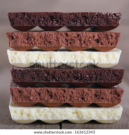 White, milk and dark chocolate on a wooden background - stock photo