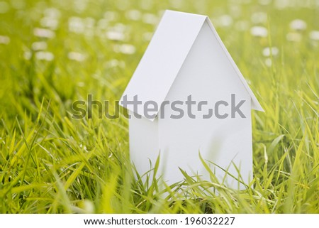 White model house made from paper over a green grass field with spring flowers in the background and copy space on the side. - stock photo