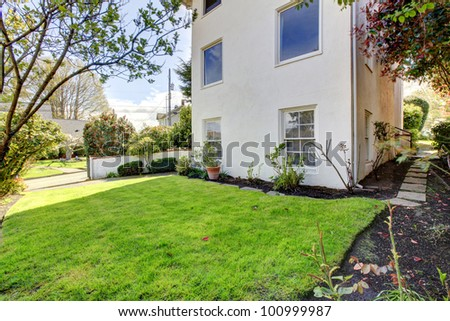 White modern house exterior with green grass and sidewalk. - stock photo