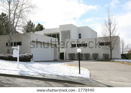 White modern style house on a hill with blank real estate sign - stock photo