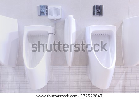 White modern urinals in public toilets - stock photo