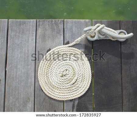 White mooring rope in a spiral pattern on a dock from above - stock photo
