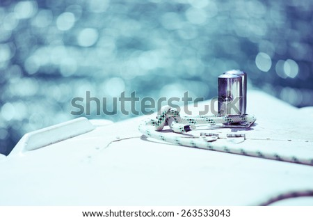 White mooring rope tied around steel anchor on boat or ship, shallow dof, tinted blue, copy space - stock photo