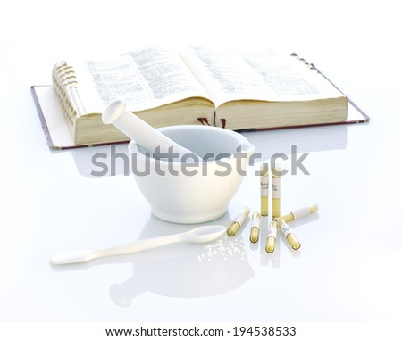 white mortar and glass tubes globules and book - stock photo