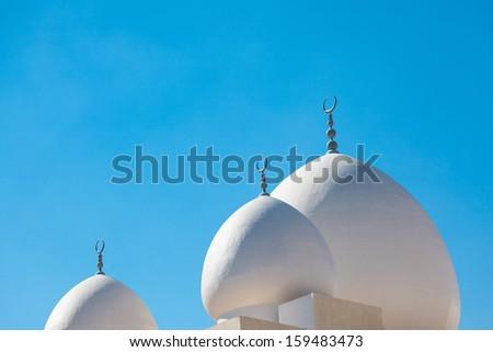 White mosque against bright blues sky, United Arab Emirates - stock photo