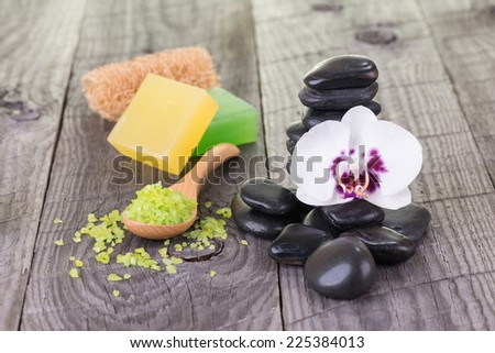White Moth orchid, soaps and green bath salt on weathered deck close up - stock photo