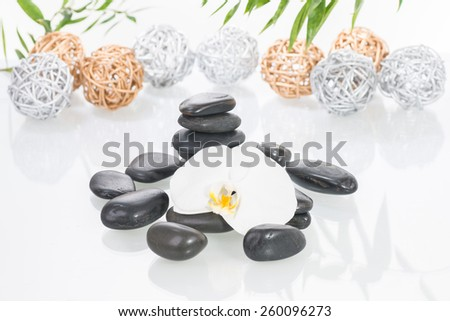 White Moth orchids, black zen stones with silver and gold twig balls over white background - stock photo