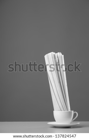 White mug and newspaper on a gray background - stock photo