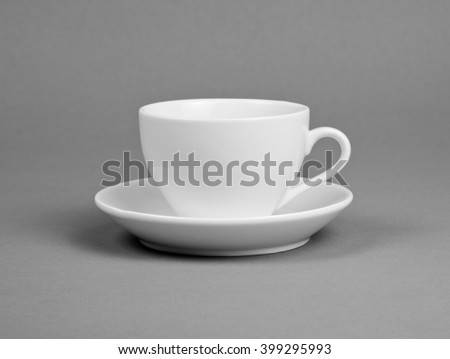 White mug and saucer on a gray background - stock photo