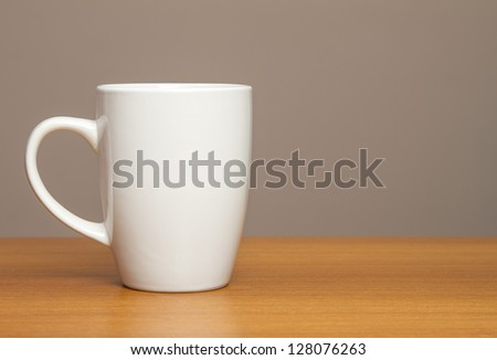 White mug on wooden table - stock photo