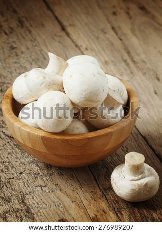 White mushrooms in a bowl on wooden table, selective focus - stock photo