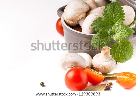 white mushrooms in pan, sliced cherry tomatoes, garlic and mint over white - stock photo