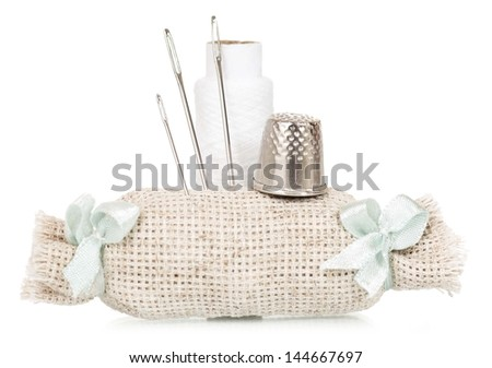 White needle bed with threads and thimble isolated on white background - stock photo