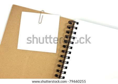 White note paper clip on brown cover note book - stock photo