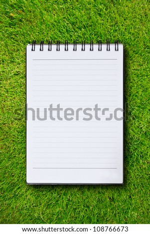 White notebook in green grass background - stock photo