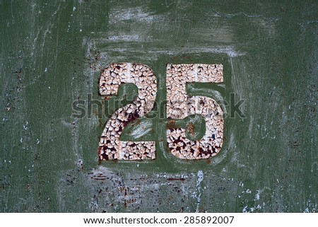 White number 25 on old metal panel painted in green  - stock photo