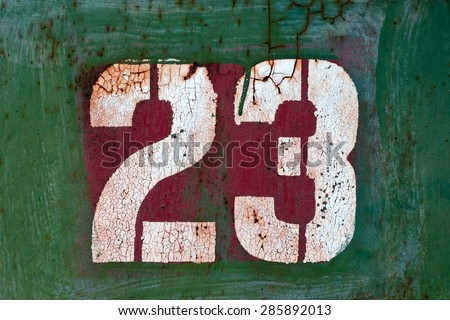White number 23 on old metal panel painted in green  - stock photo