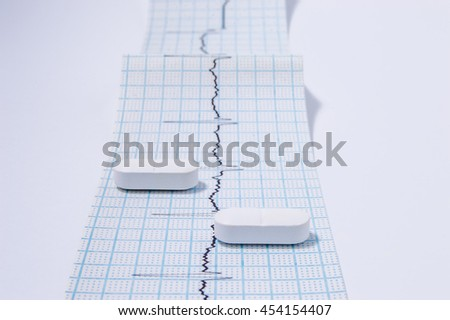 White oblong pills or tablets are on the tape with ambulatory electrocardiogram (EKG or ECG) records front view. One of the necessary medical examinations for physician in cardiology - stock photo