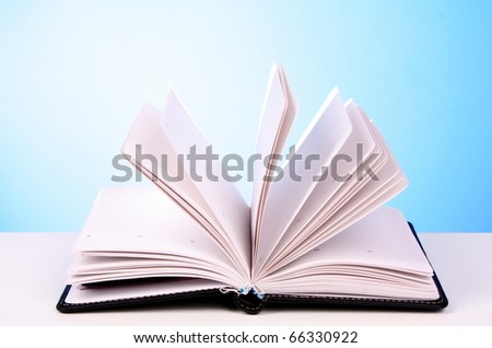 White opened book with blank pages on blue background - stock photo