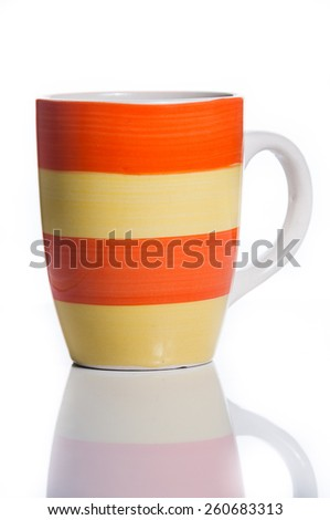 White Orange Yellow Striped Ceramic Mug with Spoon. Isolated on White - stock photo