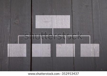 White organigram on black wooden background - stock photo