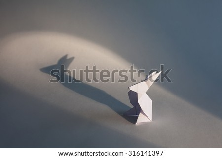 White origami rabbit isolated on white background with lights and shadows. - stock photo