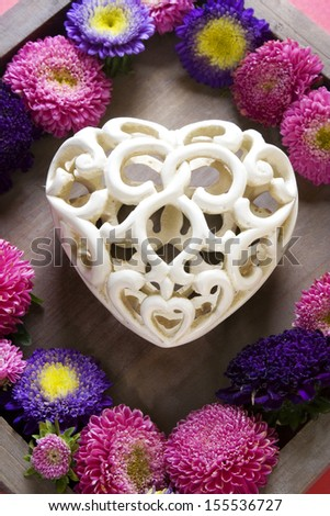 White ornate heart surrounded with flowers - stock photo
