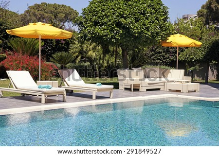 white outdoor furniture in the garden near the swimming pool for relax on beautiful summer resort - stock photo