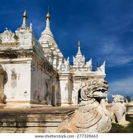 White Pagoda at Inwa ancient city with lions guardian statues. Amazing architecture of old Buddhist Temples. Myanmar (Burma) travel landscapes and destinations - stock photo