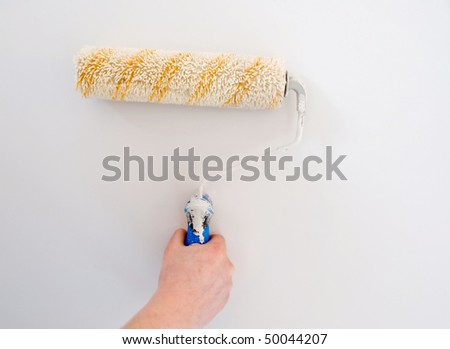 white paint roller on wall (painting wall) - stock photo