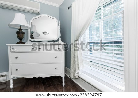 White painted dresser with mirror and lamp near window interior - stock photo