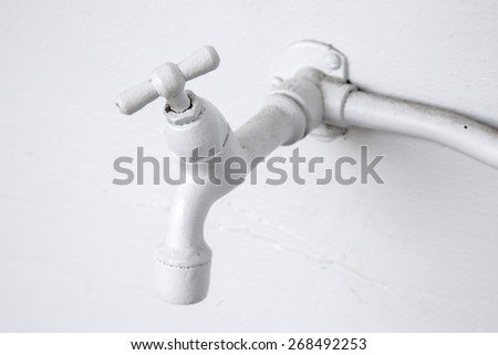 white painted water tap against white washed wall - stock photo
