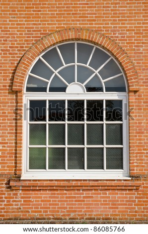 White painted wood arched window in a red brick wall . - stock photo