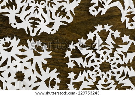 White paper christmas snowflake on a wood background - stock photo