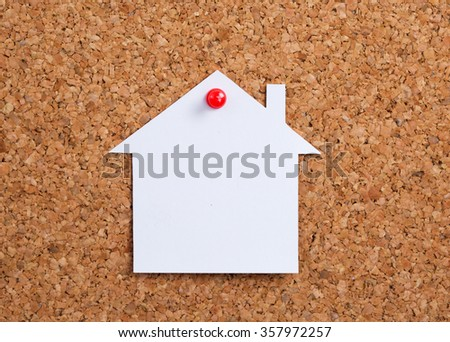White paper house on cork board - stock photo