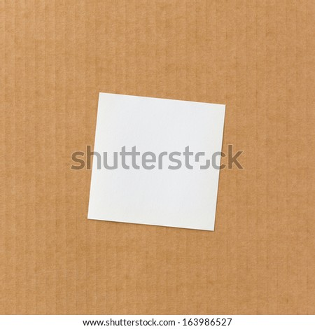 White paper note on corrugated cardboard background - stock photo