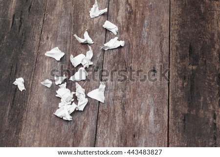 white paper note rip Pieces and crumpled on a wooden floor soft-focus  with copy space for add text above and may be used as background  - stock photo