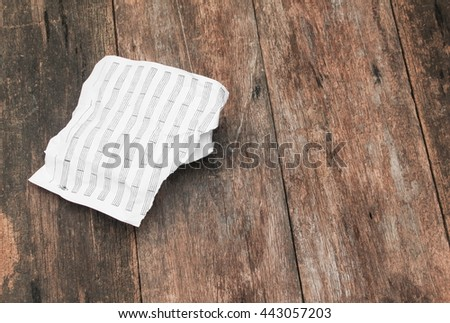 white paper sheet note rip and crumpled on a wooden floor soft-focus  with copy space may be used as background  - stock photo