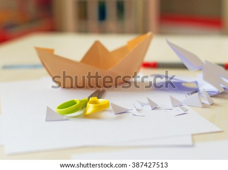 White paper sheet, scissors and origami on the table. - stock photo
