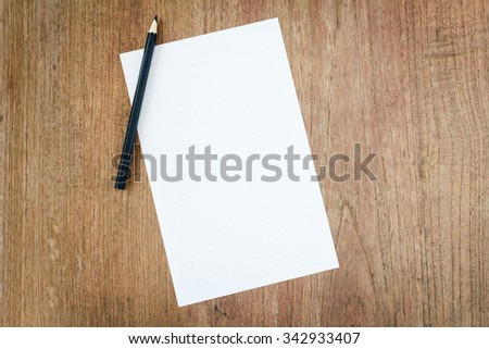 white paper with black pencil on wooden table - stock photo