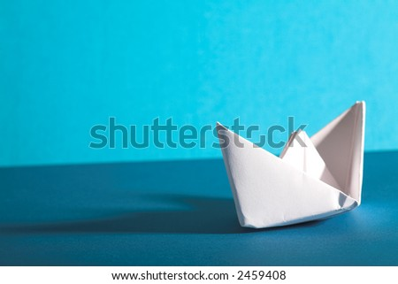 white paper yacht with shaodow on blue background - stock photo