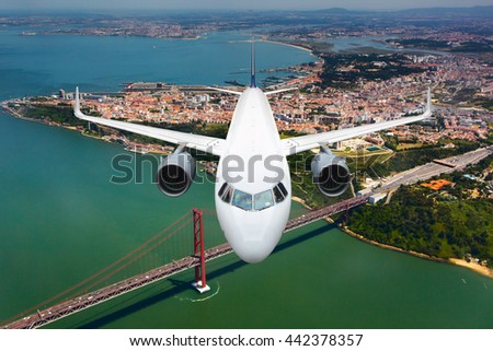White passenger airplane is flying in the blue sky over the city rooftops, bridge and the river - stock photo