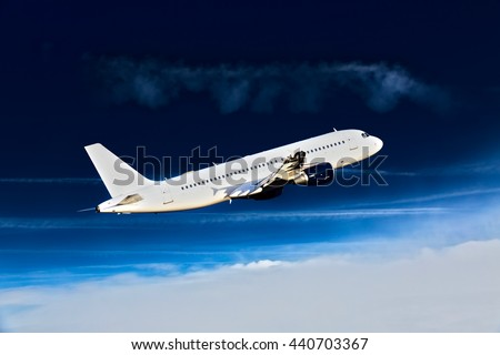 White passenger airplane with blue engines. Aircraft is climbing high in the deep-blue sky. - stock photo