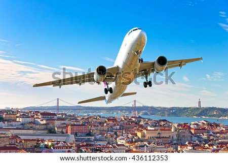White passenger airplane with left roll. Aircraft is flying in the blue sky over the city rooftops, river and bridge. - stock photo